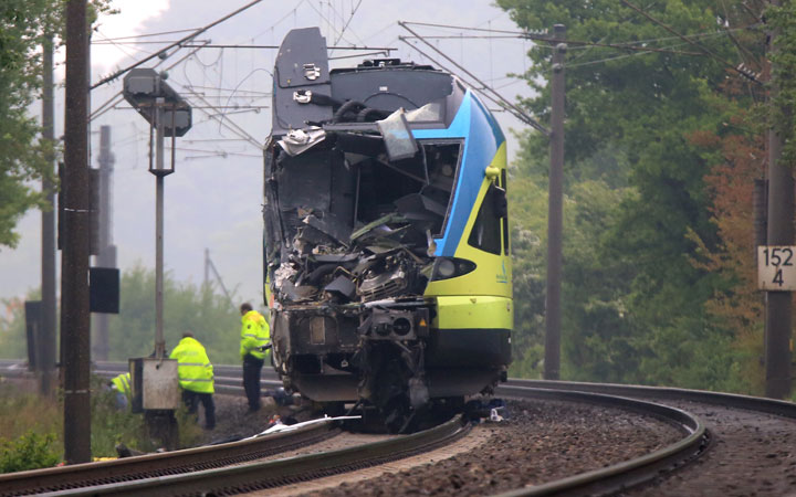 Workers are busy near the damaged train that hit a truck on a road crossing near Ibbenbueren, western Germany, Saturday, May 16, 2015.