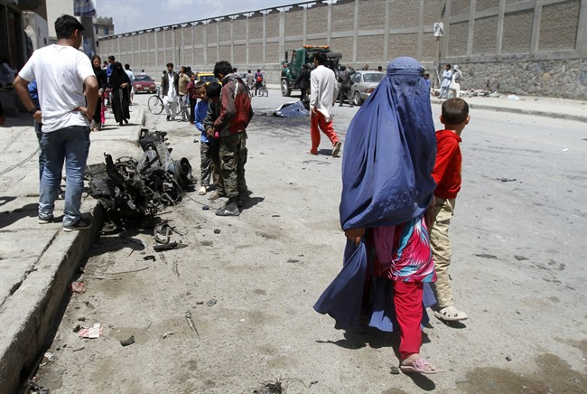 An Afghan woman walks with her son at the site of a suicide attack near Kabul's international airport in Afghanistan, Sunday, May 17, 2015.