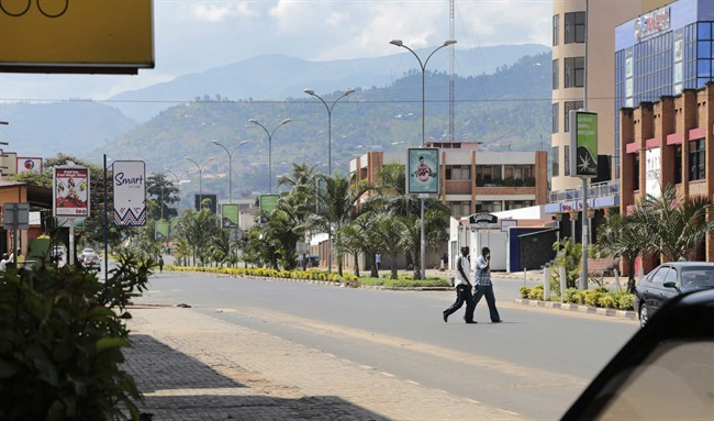 Two men walk across a deserted street in the town center of Bujumbura, Burundi, Friday, May 15, 2015. Two senior army officers and a police general accused of taking part in an attempted coup in Burundi have been arrested, a presidential spokesman said on Friday, as it became apparent that a military plot to oust President Pierre Nkurunziza had fizzled out.