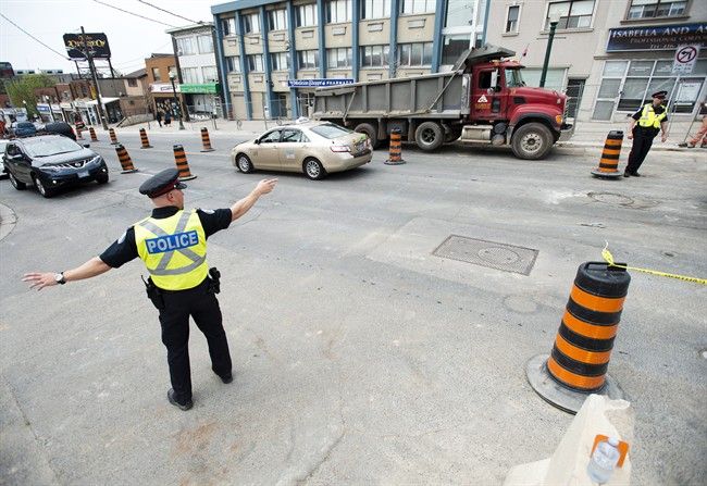 Off-duty City of Toronto police officers manage traffic in a construction zone in Toronto on Monday, May 11, 2015.