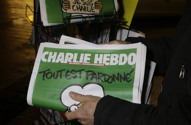 """In this Wednesday, Jan. 14, 2015, file photo, a seller of newspapers stocks several """"Charlie Hebdo"""" newspapers at a newsstand in Nice, France."""