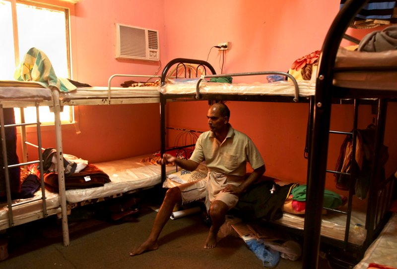 In this Sunday, May 3, 2015 file photo taken during a government organized media tour, Kuttamon Chembadnan Velayi from Kerala, India, speaks to journalists while sitting on his bed in a room he shares with seven other Indian laborers in Doha, Qatar.