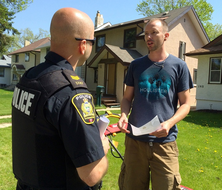A Winnipeg police officer speaks to a River Heights resident about crime.