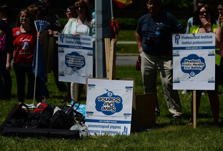 A pile of unused placards sits upside down during a rally at Tunney's Pasture in Ottawa on Tuesday, May 19, 2015.