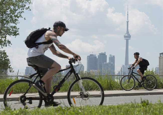 Cyclists ride past the skyline in Toronto on June 26, 2012.