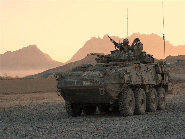 A Canadian LAV (light armoured vehicle) arrives to escort a convoy at a forward operating base near Panjwaii, Afghanistan at sunrise on Nov. 26, 2006.