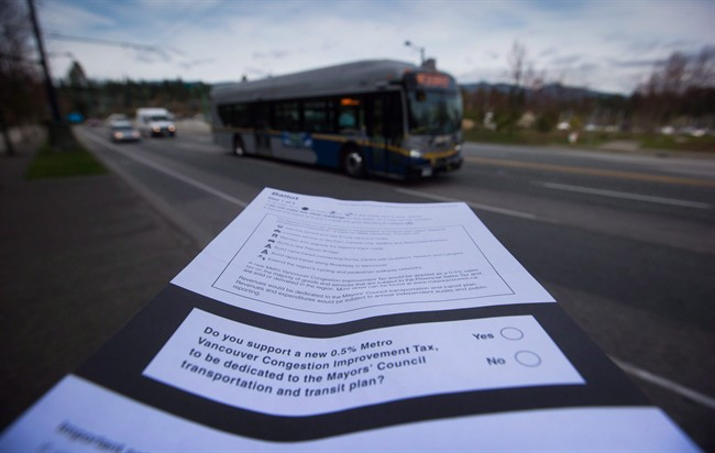 A ballot for the proposed transit tax is displayed as a bus passes by on West Georgia Street in Vancouver, B.C., on March 17, 2015. Residents of Metro Vancouver were handed an unprecedented opportunity to vote for new and improved regional transportation in a transit-tax plebiscite that both sides are confident of winning.