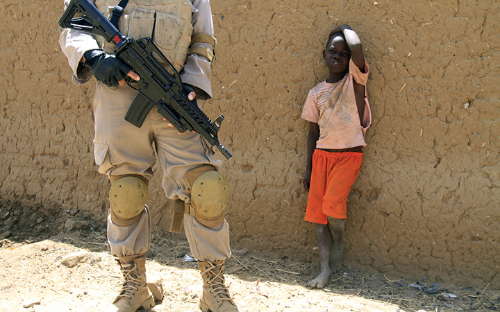 FILE: A young boy watches a United Nations peacekeeper in the North Darfur state capital of El-Fasher, on June 17, 2013.
