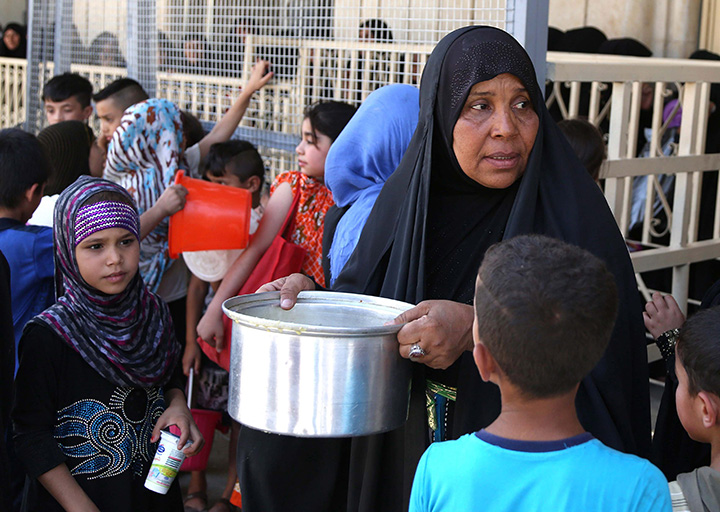 Iraqis, most of them refugees, gather for free food being distributed for Iftar, the meal after fasting, at the Abdul Khader al-Kilani mosque in Baghdad, Iraq, Tuesday, June 23, 2015.