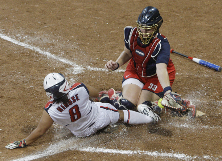 FILE - This is a  Thursday, Aug. 21, 2008. file photo of Japan's Megu Hirose scores as USA catcher Stacey Nuveman tries to apply the tag in the seventh inning in the gold medal softball game in the Beijing 2008 Olympics in Beijing. Japan won 3-1. The sports of Softball and Baseball are hoping to be included into the 2020 Olympic Games. (AP Photo/Elaine Thompson, File).