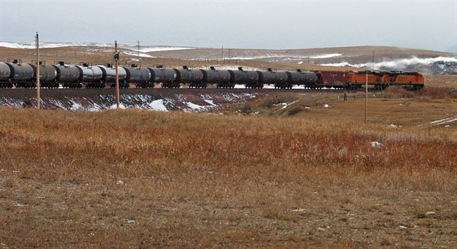 In this Nov. 7, 2013, file photo, locomotives pulling oil tanker cars begin the ascent into Glacier National Park as it travels toward the Pacific Coast near Chester, Mont.