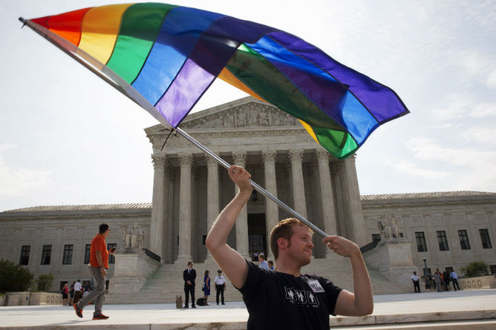 John Becker, 30, of Silver Spring, Md., waves a rainbow flag in support of gay marriage outside of the Supreme Court in Washington, Thursday June 25, 2015. The same-sex marriage ruling is among the remaining to be released before the term ends at the end of June.