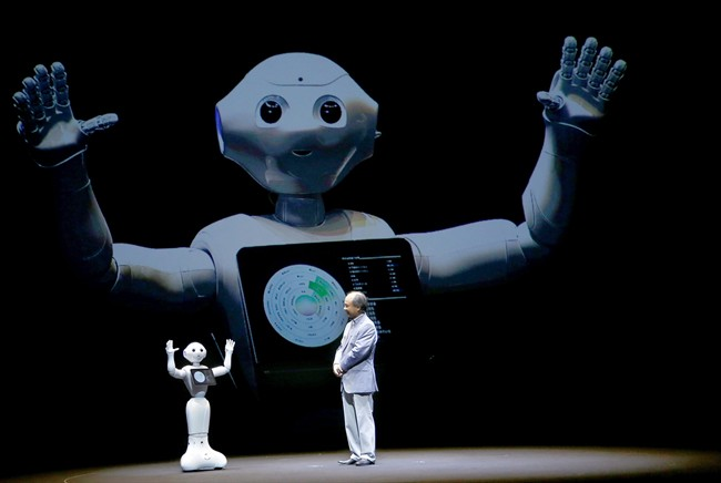 SoftBank Corp CEO Masayoshi Son speaks with the company's robot Pepper during a press conference.