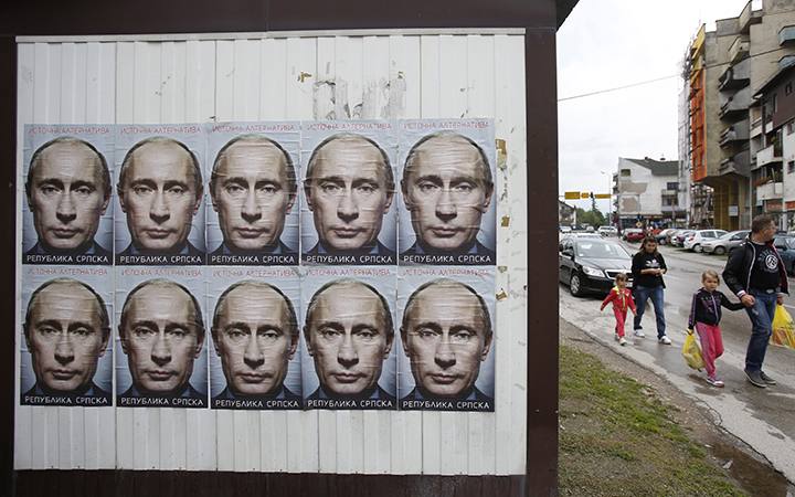 People pass by posters displaying Russian President Vladimir Putin in the town of Bratunac, near Srebrenica on Sunday June, 28, 2015, less than two weeks before the Srebrenica massacre's 20th anniversary.