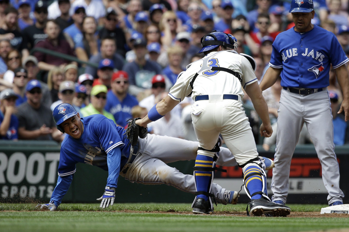 Seattle Mariners catcher Mike Zunino, center, tags Toronto Blue Jays' Ezequiel Carrera, left, out at third base as third base coach Luis Rivera looks on at the end of a triple play in the fourth inning of a baseball game Sunday, July 26, 2015, in Seattle.