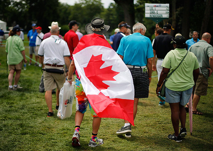 """A golf fan wears a Canadian flag while watching the first round of the U.S. Women's Open golf tournament at Lancaster Country Club in Lancaster, Pa., on July 9, 2015. Canadian Open organizers are adding a lot more red and white to the expanse of green at Glen Abbey Golf Club. First-year tournament director Brent McLaughlin heard from players that there's not enough """"Canadiana"""" at the RBC Canadian Open."""