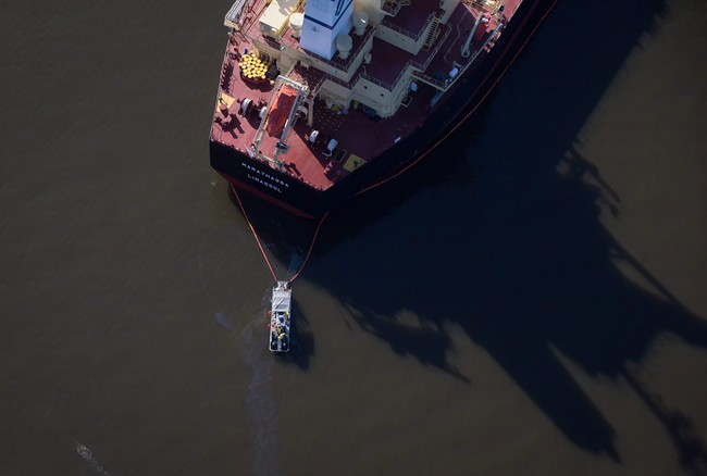 A spill response boat monitors a boom placed around the bulk carrier cargo ship MV Marathassa after a bunker fuel spill on Burrard Inlet in Vancouver, B.C., on April 9, 2015.