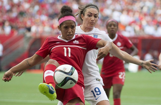 Canada's Desiree Scott fights for the ball with England's Jodie Taylor during second half of FIFA World Cup quarter-final soccer action in 2015.