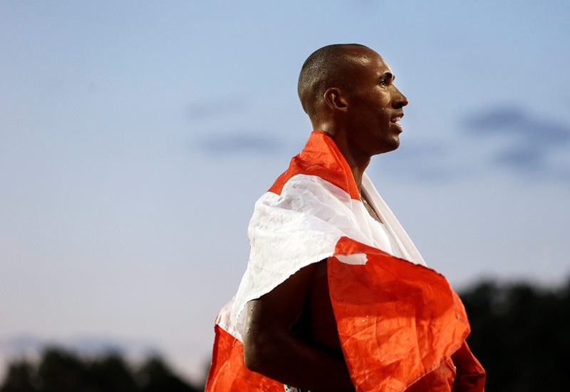 Decathlon champion Damian Warner of Canada wears a national flag following his win in the men's decathlon 1500 meter run at the Pan Am Games Thursday, July 23, 2015, in Toronto.