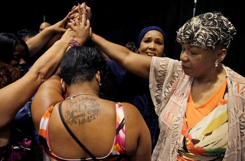 In this July 8, 2015 file photo, Gwen Carr, mother of Eric Garner, right, joins women whose families members were killed by police officers after New York Gov. Andrew Cuomo signed an executive order that puts the office of the state attorney general in charge of investigating killings by police.