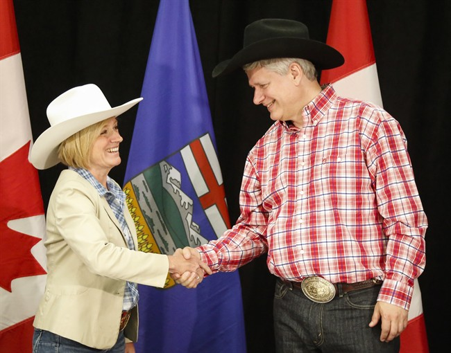Alberta Premier Rachel Notley, left, greets Prime Minister Stephen Harper with a handshake in Calgary, Alta., on Monday, July 6, 2015.