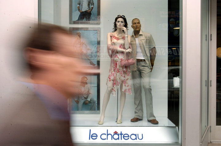 Pedestrians walk past retail clothing displays at a Le Chateau store.