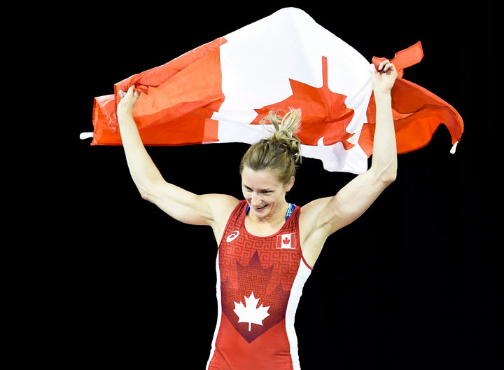Gene Morrison of Canada raises the Canadian flag after defeating Thalia Mallqui of Peru in the women's freestyle 48kg final during the Pan American Games in Toronto on Thursday, July 16, 2015. Morrison won gold.
