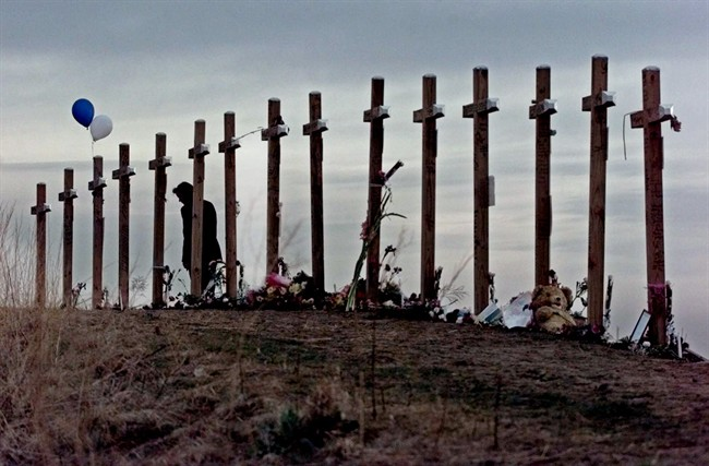 FILE - This April 28, 1999 file photo shows a woman standing among 15 crosses posted on a hill above Columbine High School in Littleton, Colo., in remembrance of the 15 people who died during a school shooting on April 20, 1999.
