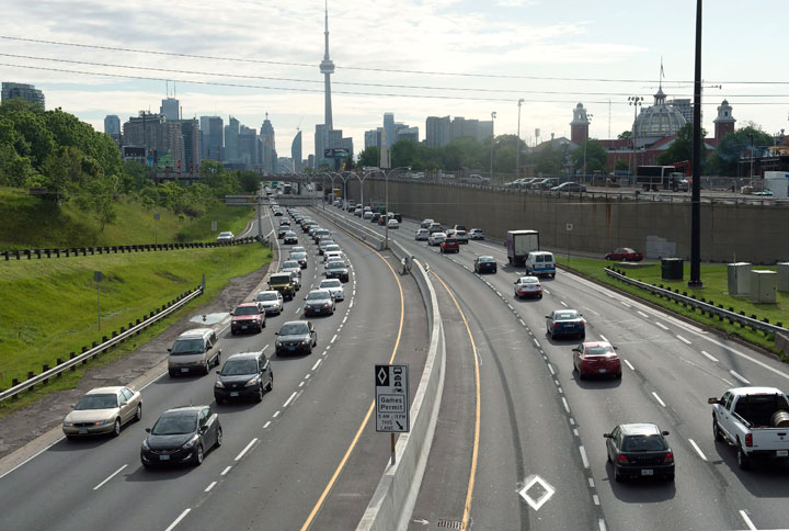 Vehicles crawl past the nearly empty Pan Am high-occupancy vehicle lanes as morning rush hour traffic crawls in Toronto on Monday, June 29, 2015.