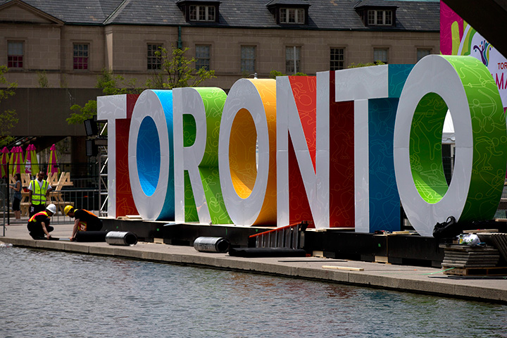 Workers erect giant letters spelling out Toronto in Nathan Phillips Square as they prepare for the Pan Am Games,.
