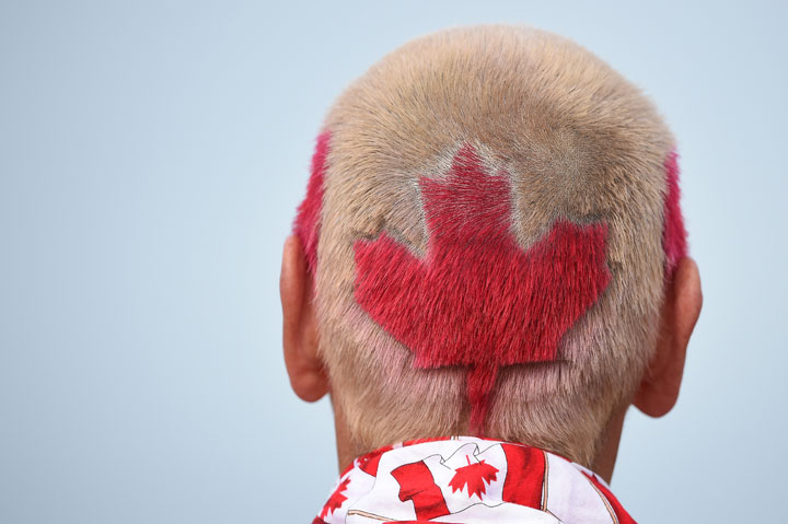 A fan sports a Canadian flag hairstyle as he follows Graham Delaet of Canada during the first round of the 144th Open Championship at The Old Course on July 16, 2015 in St Andrews, Scotland.