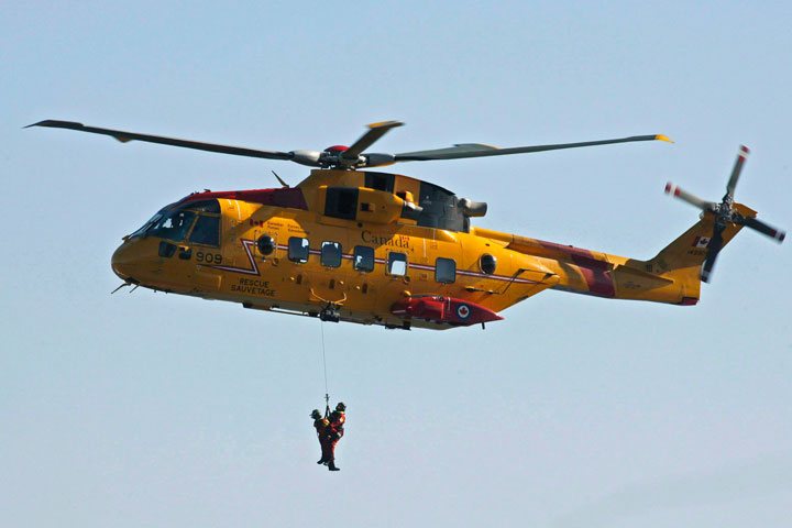 FILE - Search and rescue technicians are hoisted by a Cormorant helicopter.