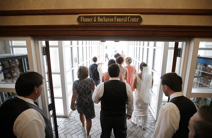 In this June 19, 2015 photo, the wedding party make their way down a hallway towards the open air courtyard where Danessa Molinder and Billy Castrodale are getting married at the Community Life Center, in Indianapolis. The centre sits on cemetery land near a funeral home and also has hosted proms and community banquets.