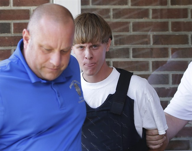 FILE - In this June 18, 2015, file photo, Charleston, S.C., shooting suspect Dylann Storm Roof, center, is escorted from the Sheby Police Department in Shelby, N.C. FBI director James Comey says Roof, the gunman in the Charleston church massacre should not have been allowed to purchase the gun used in the attack, and on July 10 attributed the problem to incomplete and inaccurate paperwork related to an arrest of Roof weeks before the shooting. (AP Photo/Chuck Burton, File).