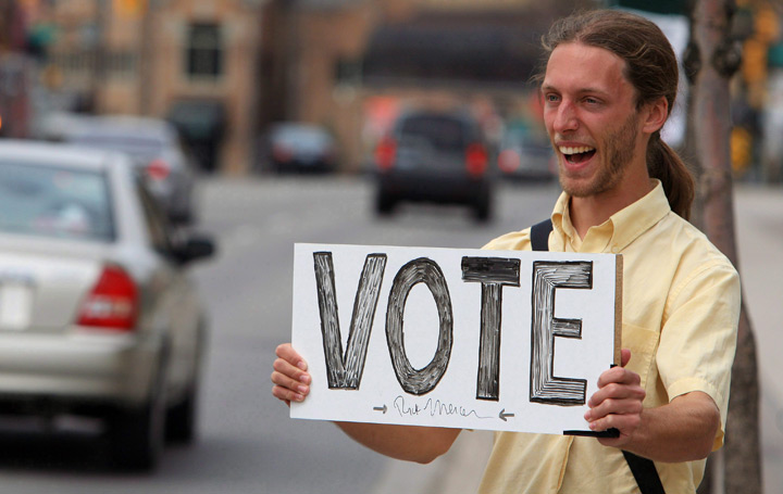 Man holds a sign encouraging people to vote