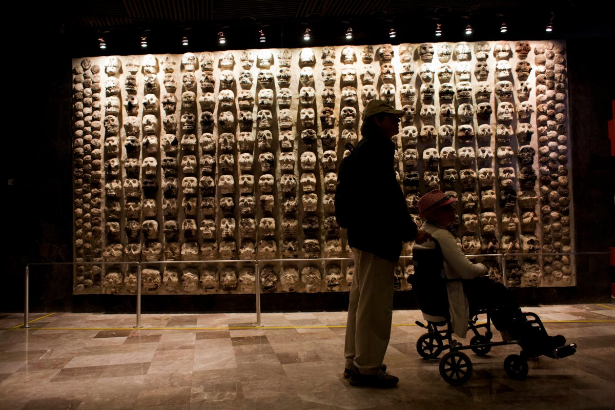 A man pushes a woman in a wheelchair past a wall of stone skulls that represent sacrificial victims, at the entrance to the Templo Mayor museum in central Mexico City, Friday, Aug. 7, 2015. The Templo Mayor museum has put on display for the first time an offering dedicated to Xochipilli, the Aztec god of singing, dancing, and the morning sun.