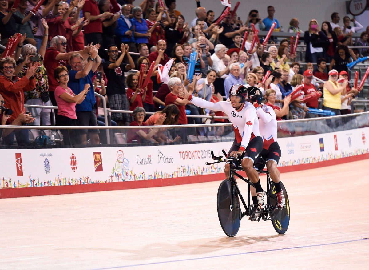 Alexandre Cloutier and Daniel Chalifour of Canada react to the crowed after winning gold in the 4000m tandem pursuit track cycling event during the Parapan Am Games in Milton, Ont., on Monday, August 10, 2015.