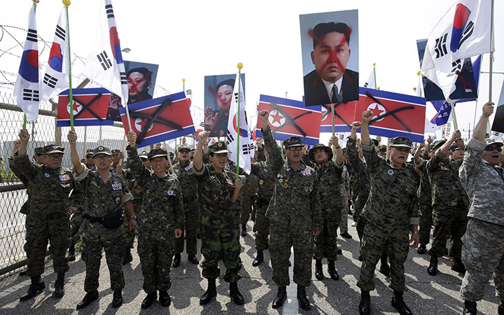 Members of the Korean Disabled Veterans Association by Agent Orange in Vietnam War, shout slogans as they hold mock North Korean flags and defaced images of North Korean leader Kim Jong Un during a rally denouncing the North Korea in front of the Unification Bridge near the border village of Panmunjom in Paju, north of Seoul, South Korea, Thursday, Aug. 13, 2015.