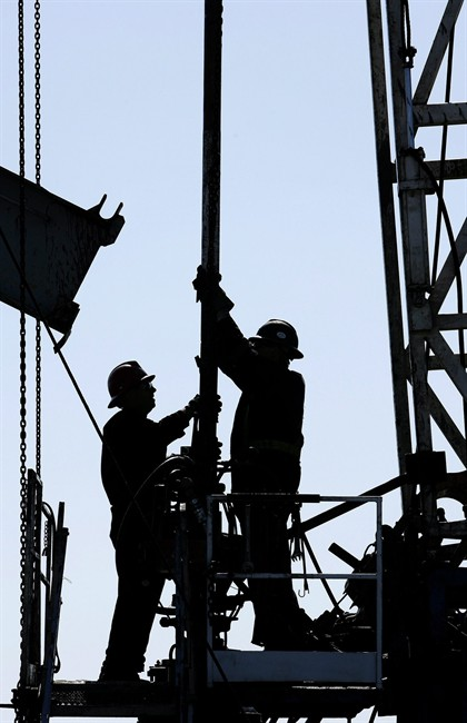 A service rig crew performs maintenance and repair work on an oilfield pumpjack and well head site in Alberta on June 20, 2007.