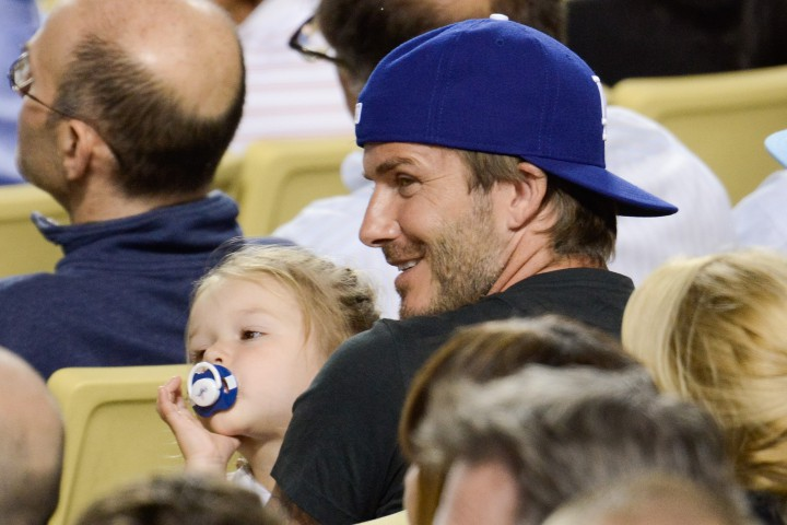 David Beckham sits with daughter Harper at Dodger Stadium in Los Angeles, California on August 27, 2013.