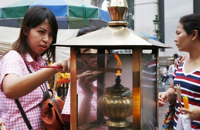In this Aug. 26, 2015, file photo, worshippers light sticks of incense at the Erawan Shrine at Rajprasong intersection, in Bangkok, Thailand. (AP Photo/Penny Yi Wang, File).