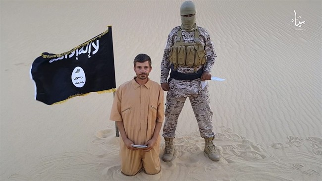 This image made from a militant video posted on a social media site on Wednesday, Aug. 5, 2015, shows a militant standing next to 30-year-old Tomislav Salopek, kneeling down as he reads a message at an unknown location. An online image purports to show the Croatian hostage being held by an Islamic State affiliate in Egypt has been beheaded.