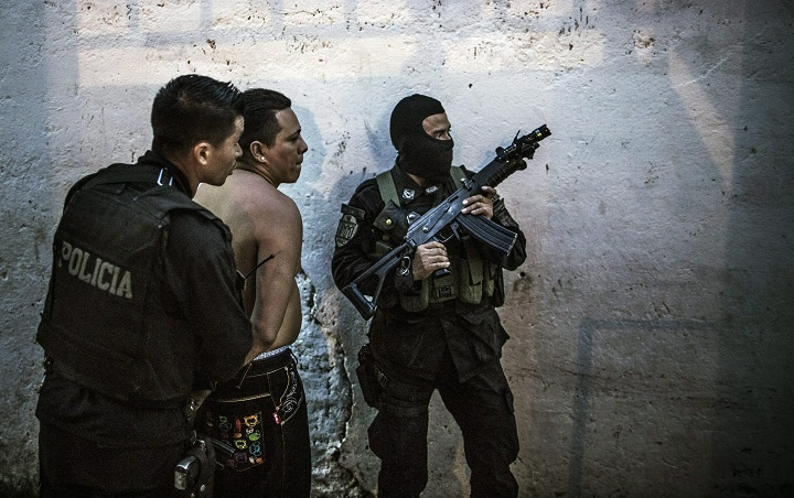In this May 28, 2015 photo, members of the fast response police units, known as Halcones, detain a suspected gang member.