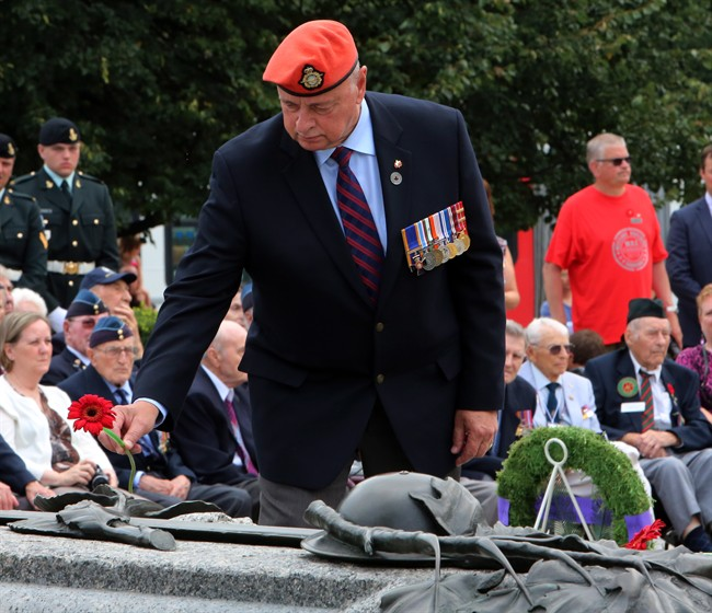 Veterans Affairs Ombudsman Guy Parent lays a flower at the Tomb of the Unknown Soldier, during a commemoration ceremony of the 70th anniversary of the end of the Second World War in the Far East, or V-J Day (Victory Over Japan) at the National War Memorial in Ottawa on Saturday, August 15, 2015.