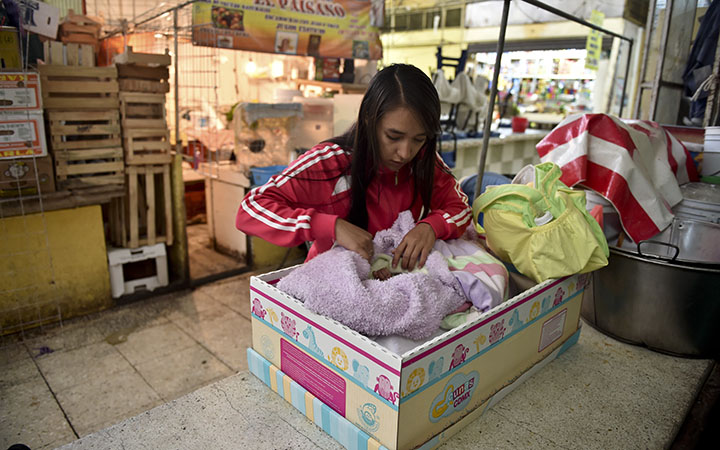 A young mother looks at her one-month-old baby girl at her work in a market of the Romero Rubio suburb in Mexico City, on August 24, 2015.