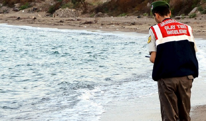 A Turkish officer stands over the body of a young boy, believed to be a Syrian refugee, washed ashore near the Turkish resort of Bodrum on Wednesday.  The original photo can be seen below. Viewer discretion is advised.