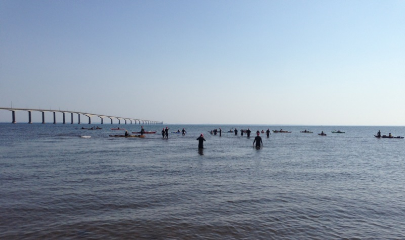 Swimmers leave the water near The Confederation Bridge, which spans the Northumberland Strait.