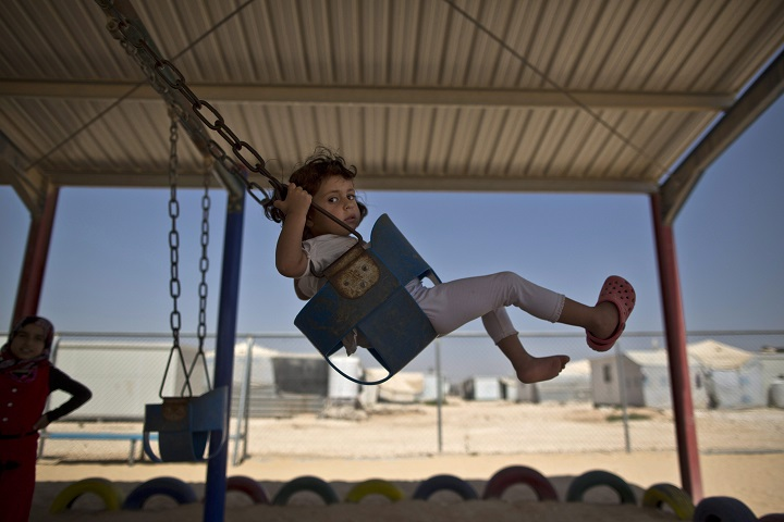 A Syrian girl plays on a swing while she and other children celebrate the first day of the Eid al-Fitr holiday that marks the end of the holy fasting month of Ramadan at Zaatari refugee camp, in Mafraq, Jordan, Friday, July 17, 2015.