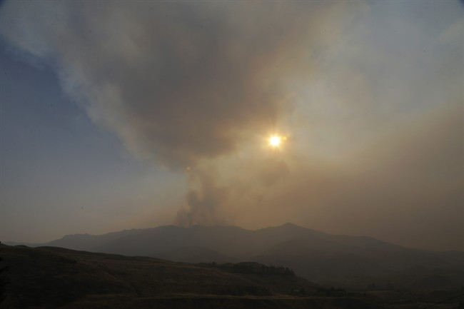 Smoke rises from a ridge above Pateros, Wash., as the sun sets Tuesday, Aug. 25, 2015. The town is located in between where wildfires are currently burning in Chelan, Wash., and Okanogan, Wash., but Pateros suffered the loss of hundreds of homes in fires that hit the area in 2014.