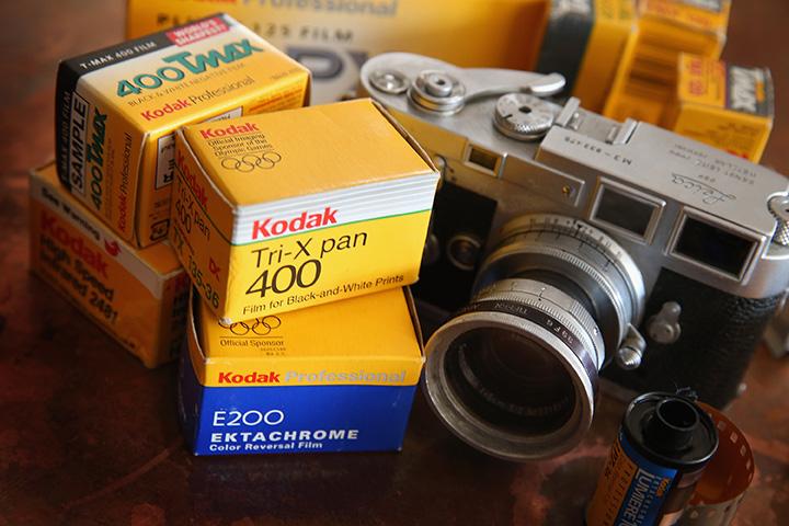Kodak film is seen alongside a vintage Leica M3 35mm rangefinder camera.